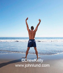 Image of a man stretching and exercising at the beach. He is facing the Ocean and the sky is blue with no clouds in site.Blue swim trunks.